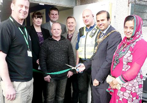 Pendle mayor Asjad Mahmood cuts the ribbon at the refurbished youth club, watched by guests including MP Andrew Stephenson (back, centre).