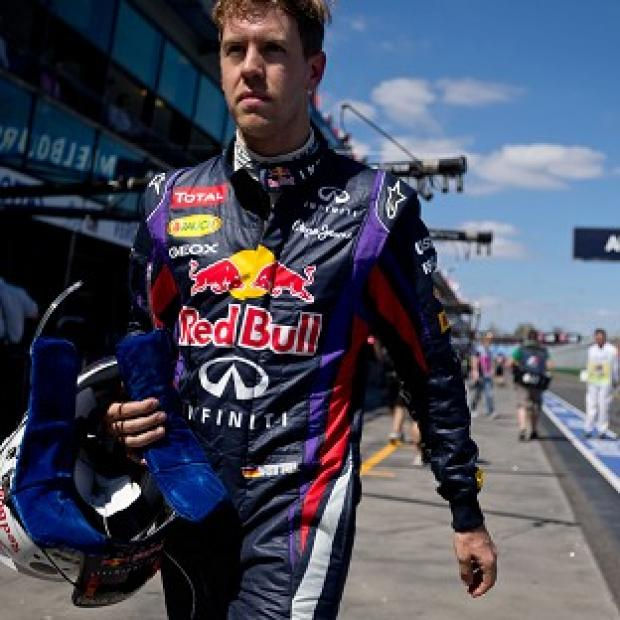 Red Bull driver Sebastian Vettel walks along the pit lane after the first practice session (AP)