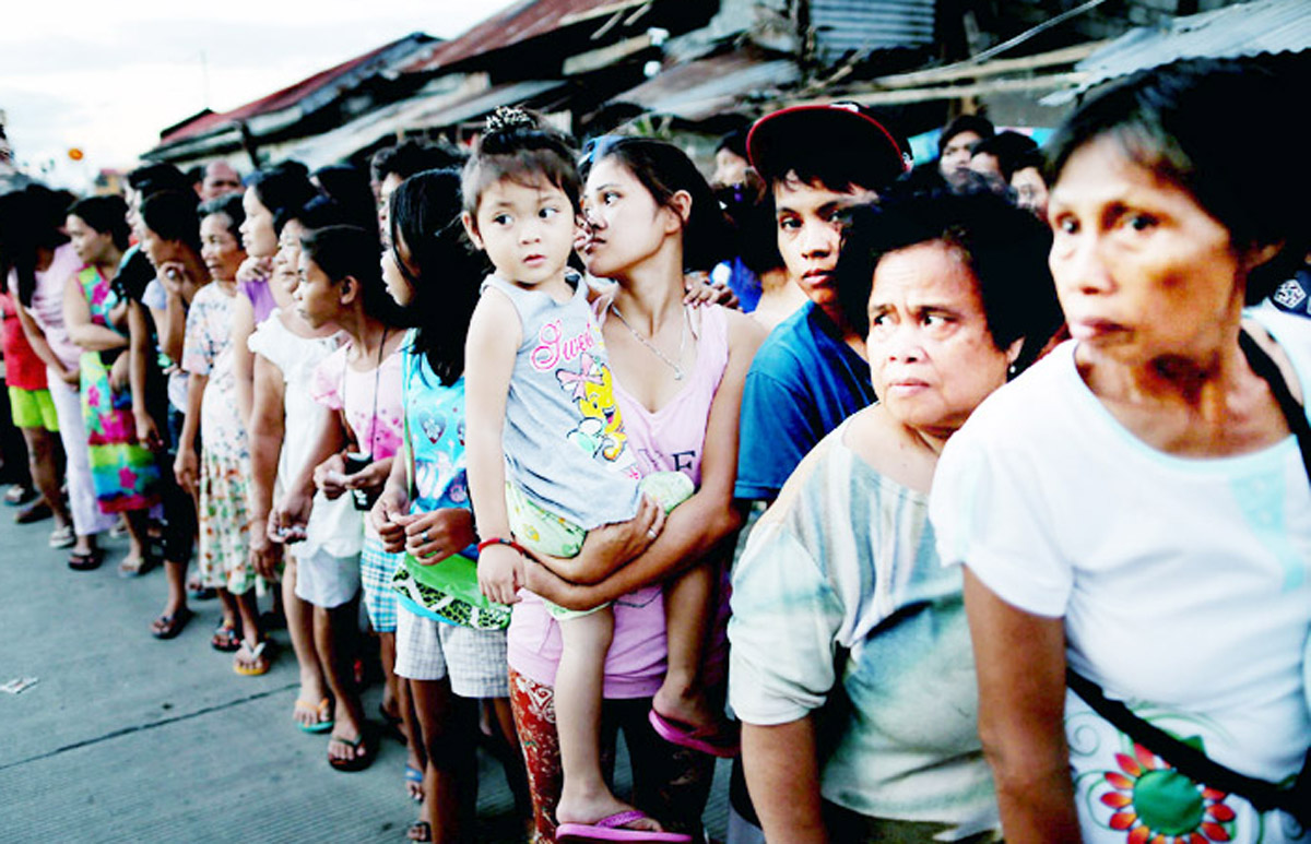 Fillipinos queue for aid after Typhoon Haiyan