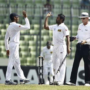 Dilruwan Perera, centre, celebrates with a team-mate after finishing with five for 109 (AP)