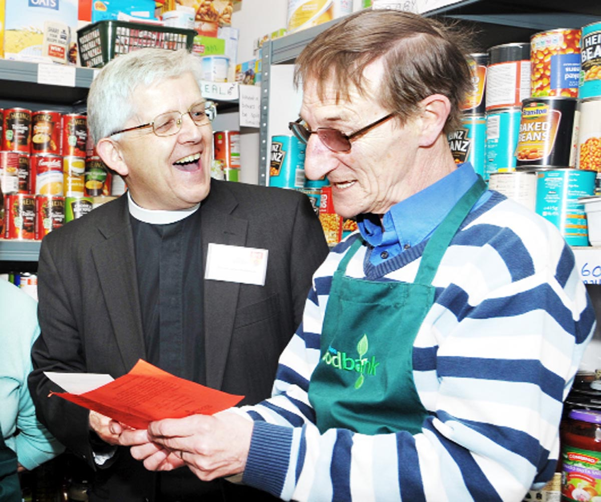The Bishop of Blackburn, the Rt Rev Julian Henderson, shares a joke with a volunteer during a visit to the Blackburn Foodbank