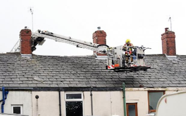 Burnley and Pendle Citizen: Residents look on as firefighters clear up some of the debris on Empress Street