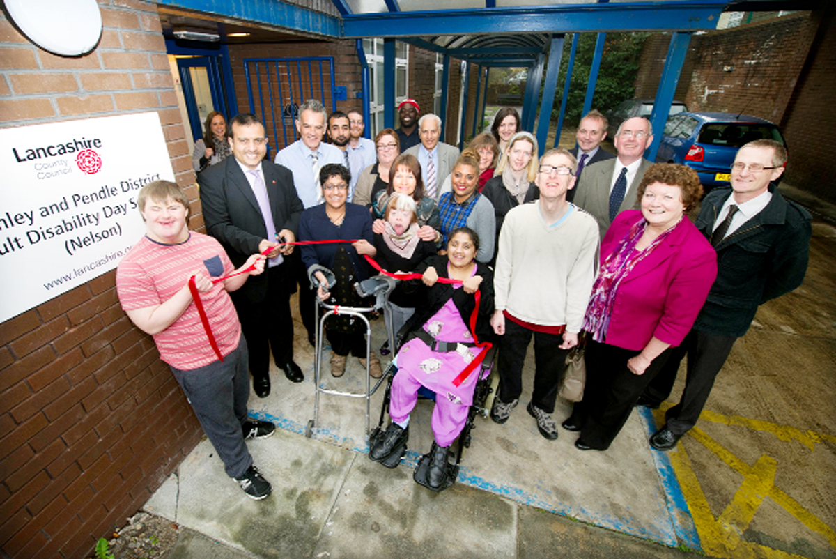 County Coun Mohammed Iqbal (Brierfield and Nelson North) cuts the ribbon surrounded by service users and staff