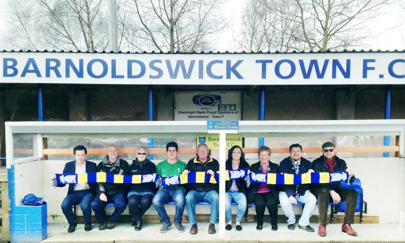 Goalkeeper Lyle Davy and Coun Paul White (far left) with new board members and investors at Barnoldswick Town