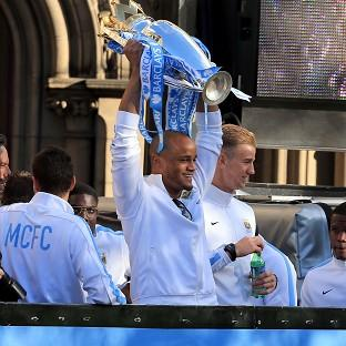 Vincent Kompany lifts the Barclays Premier League trophy during Manchester City's victory parade