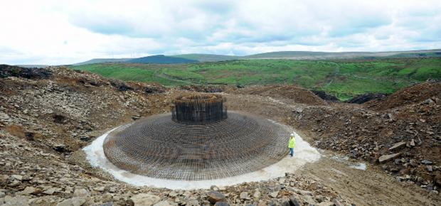 Burnley and Pendle Citizen: A worker stands next to the gigantic base for the turbine. The windfarm at present. Pictures: JADE DOHERTY