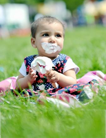 Eight-month-old Kinza Hussain looks like she's thoroughly enjoying her ice cream in the sun  in Witton Park yesterday