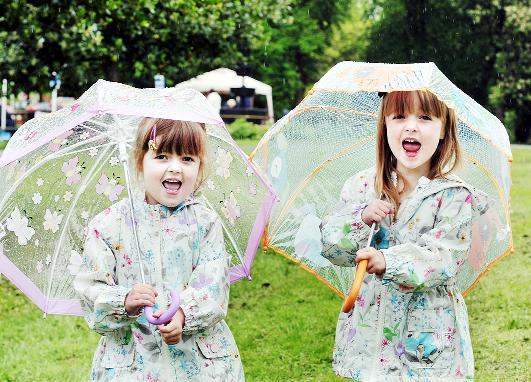Burnley and Pendle Citizen: Twins Jasmine and Phoebe Anthony shelter themselves from last weekend's rain
