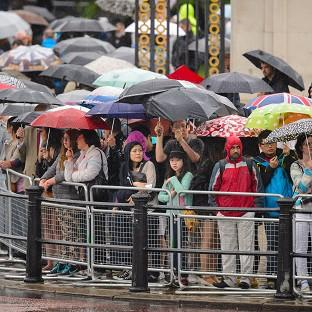 Spectators sheltering from heavy rain as they watched the f