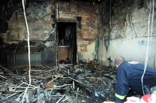A fire officer inspects damage at the house.