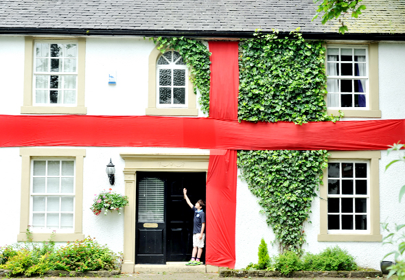 Alex Bendell, 10, outside his house in Pleasington which has been transformed into a giant England flag