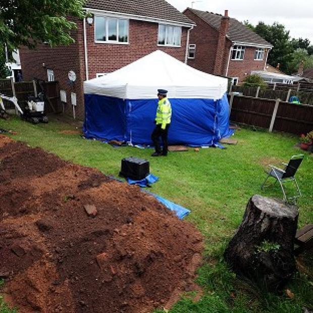 Burnley and Pendle Citizen: Police in the garden of a house in Mansfield, where the remains of William and Patricia Wycherley were discovered