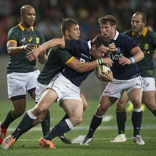 South Africa's Handre Pollard, centre left, tackles Scotland's Nick De Luca (AP)