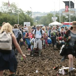 Burnley and Pendle Citizen: A man takes a break from pulling his luggage trolley along in the mud at the Glastonbury Festival