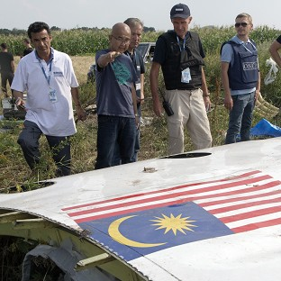 Investigators examine a piece of the crashed Malaysia Airlines Flight 17 in Petropavlivka, eastern Ukraine (AP)