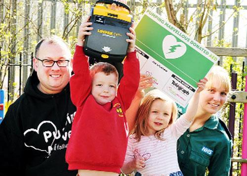 Nick Hartshorne Evans of Pumping Marvellous and paramedic Cheryl Pickstock present a defibrillator bought with a Gannett grant to Rosegrove Nursery and Rosegrove Infants,  Burnley, pupils Loagan Kennerley and Sadie Nerney
